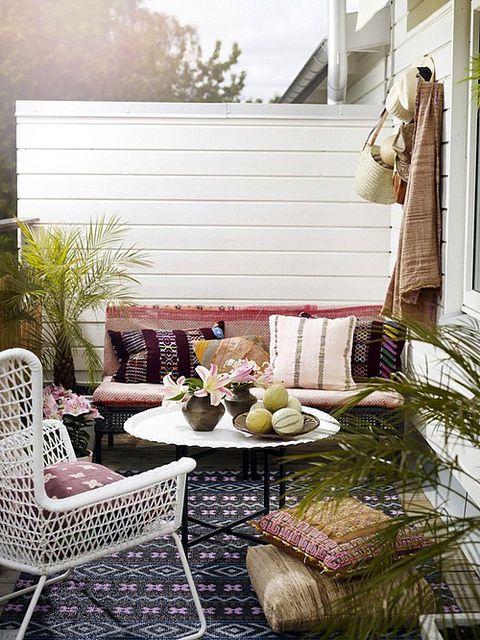 una piccola terrazza boho chic con una panca e una sedia, tessuti e cuscini boho e un po 'di verde in vaso
