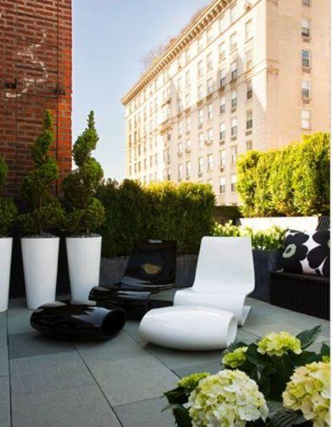 una terrazza monocromatica minimalista con piante in vaso e fiori, una sedia stravagante in bianco e nero, grandi fioriere bianche