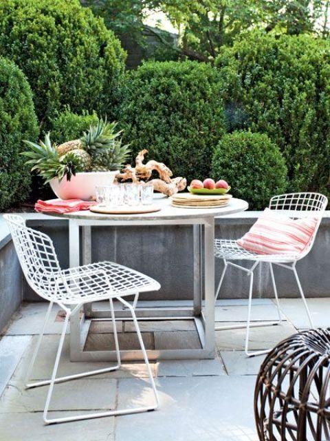 una piccola terrazza contemporanea con una zona pranzo, sedie in filo metallico, un tavolo in metallo e legno e un pouf in rattan