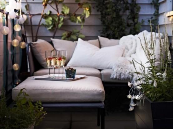 una piccola terrazza contemporanea con piante in vaso, mobili imbottiti neutri e luci
