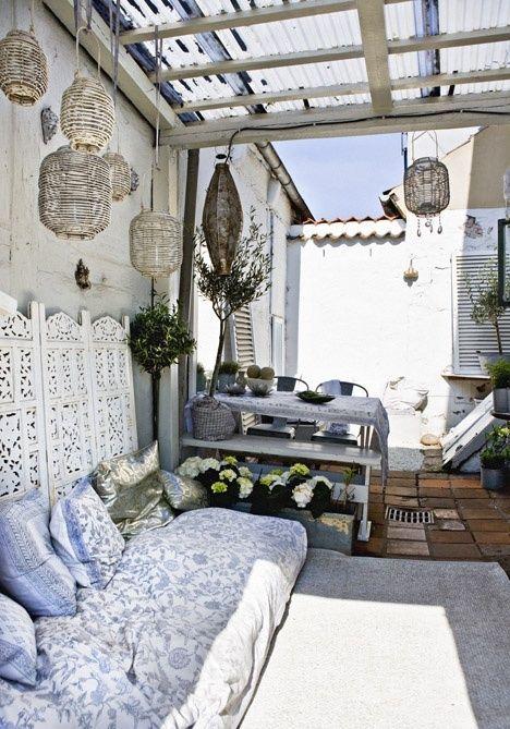 una terrazza boho chic neutra con alcuni mobili vintage, lanterne in rattan, piante in vaso e fiori