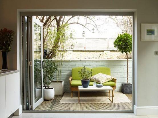 una piccola e accogliente terrazza moderna della metà del secolo con piante in vaso, un divano verde, un tappeto e un tavolino da caffè