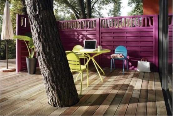 una piccola terrazza luminosa con un muro fucsia, mobili giallo brillante, una sedia blu e un comodo spazio di lavoro