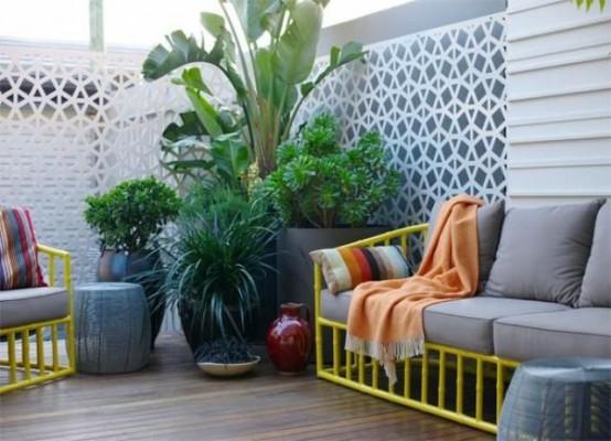 una piccola terrazza contemporanea con mobili giallo brillante e tappezzeria grigia più molta vegetazione in vaso