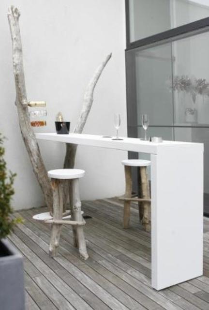 una piccola terrazza minimalista con un vecchio albero e un elegante piano di lavoro bianco che può essere utilizzato come bancone da bar o scrivania