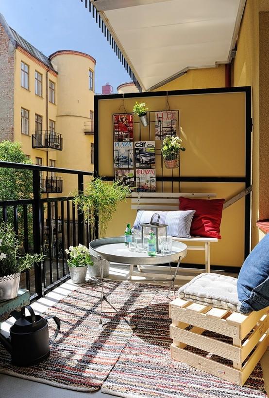 una piccola terrazza con cassa e mobili in metallo, tappeti, piante in vaso e una griglia con alcune riviste e piante