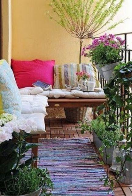 una luminosa terrazza boho con fiori in vaso e vegetazione, una panchina con cuscini colorati e fantasia e un tappeto
