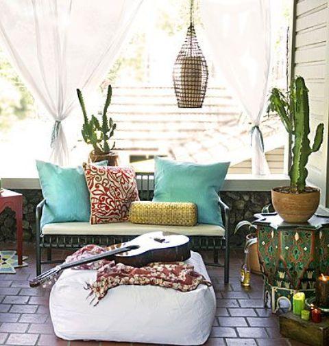 una piccola terrazza boho con mobili intagliati, un ottomano bianco, una lanterna a candela e tessuti colorati