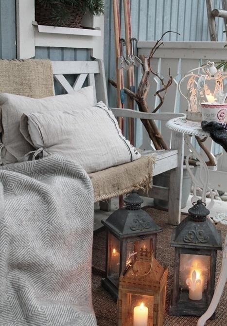 una piccola terrazza rustica con mobili vintage imbiancati, lanterne a candela, rami e sci