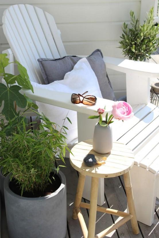 un piccolo angolo terrazza accogliente con un lettino whiet, uno sgabello e piante in vaso sui lati
