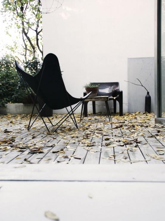 una semplice terrazza monocromatica moderna della metà del secolo con un paio di sedie nere e un tavolino