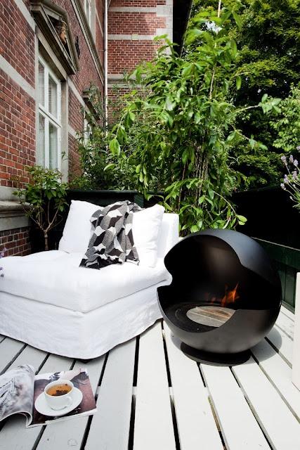 una piccola terrazza contemporanea con un focolare nero, un lettino bianco e molto verde per la freschezza e la privacy