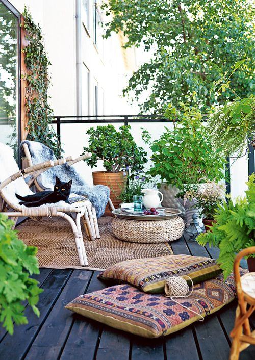 una rilassante terrazza boho con mobili in rattan, un ottomano in vimini, cuscini boho, vegetazione in vaso e fiori
