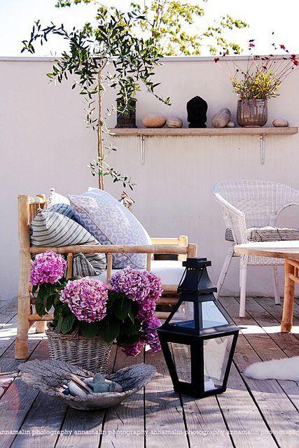 una piccola terrazza eclettica con mobili in rattan e vimini, lanterne a candela e piante e fiori in vaso