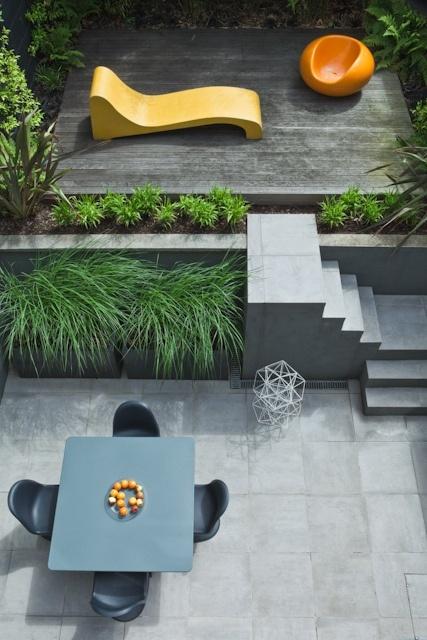 una piccola terrazza minimalista con mobili da salotto luminosi, uno spazio da pranzo laconico