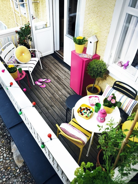 una piccola terrazza colorata con mobili semplici e luminosi, tessuti colorati e rigati, contenitori e piante e fiori in vaso