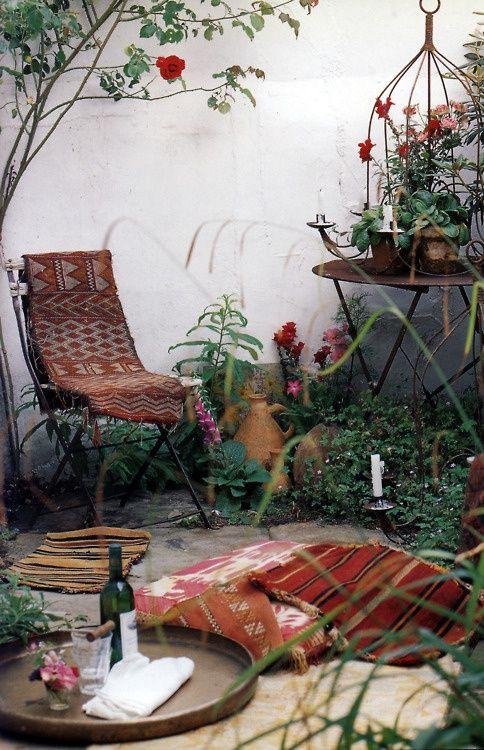 una terrazza vintage boho con mobili forgiati, tessuti boho, molte candele e un grazioso ambiente da picnic