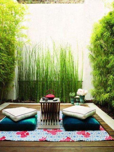 una piccola terrazza zen con un tappeto, cuscini e un piccolo tavolino da caffè e tanto verde e bambù intorno