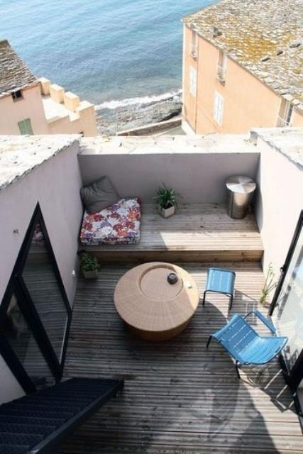 una piccola terrazza con vista sulla spiaggia, sedie blu, un tavolo di vimini e un cuscino luminoso più uno più piccolo