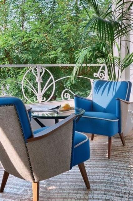 un elegante terrazzino con sedie imbottite blu, un tappeto e un tavolino in vetro