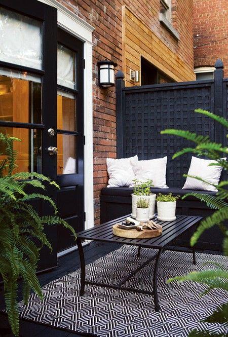 una piccola terrazza lunatica con mobili neri, tappeti e molta vegetazione in vaso per rinfrescare lo spazio