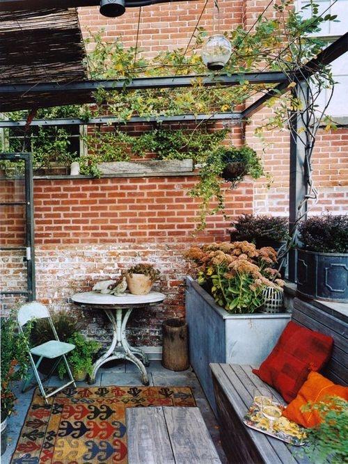 una piccola terrazza shabby chic con mobili rustici e vintage, tappeti boho e vegetazione e fiori in vaso