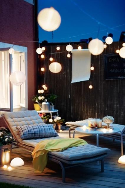 una piccola terrazza con comodi mobili contemporanei, luci, fiori e vegetazione in vaso