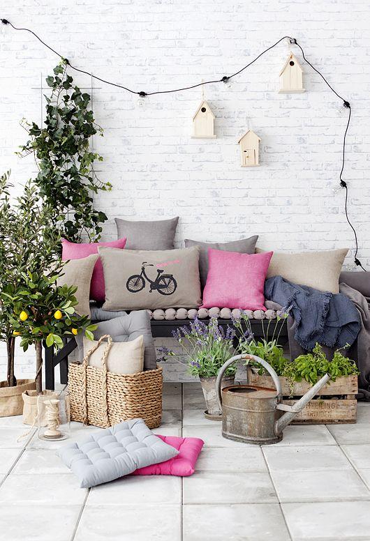 una piccola terrazza colorata con una panchina e cuscini luminosi, piante in vaso e fiori più luci