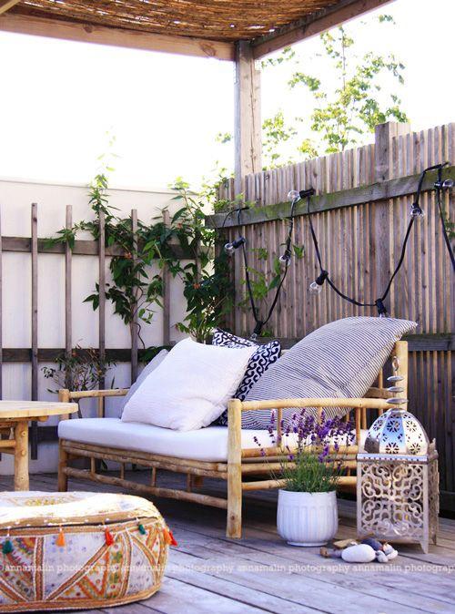 una piccola terrazza boho con lanterne a candela, mobili in rattan, vegetazione in vaso e fiori e luci