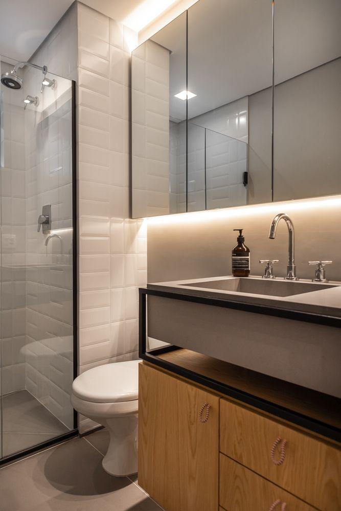 Il bagno è fatto con il bianco con tocchi neri per il dramma, un lavabo in legno, un lavandino in cemento e un grande armadio a specchio