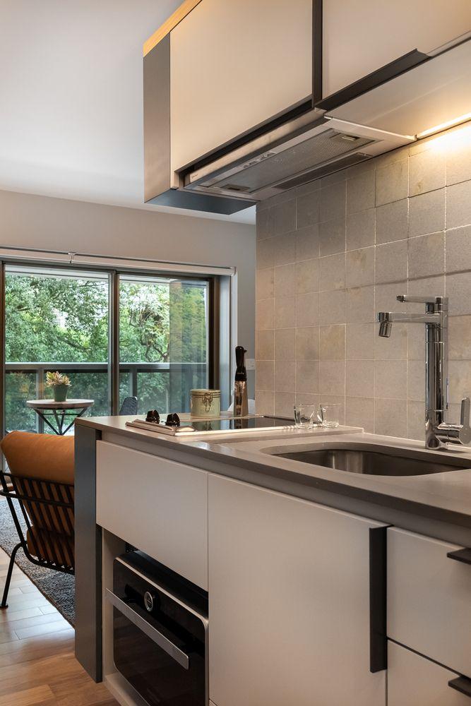La cucina è piuttosto piccola, ci sono armadi bianchi eleganti, un backsplash di piastrelle neutre e luci aggiuntive