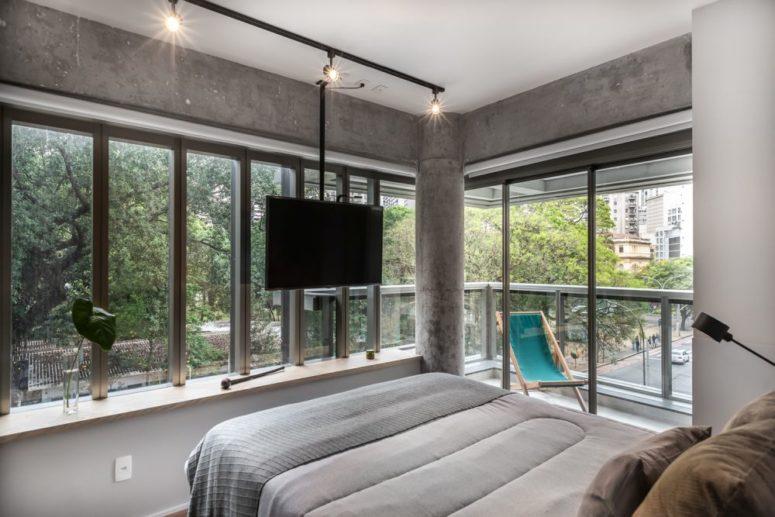 La camera da letto principale è in cemento, c'è un pilastro e due pareti vetrate più un accesso al balcone d'angolo