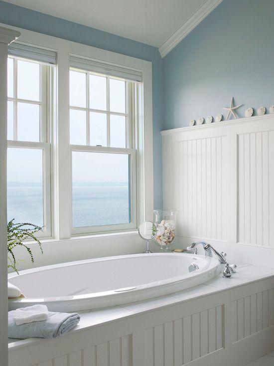 un bagno tradizionale ispirato al mare fatto in bianco e blu, con una vasca ovale incassata e una splendida vista sul mare