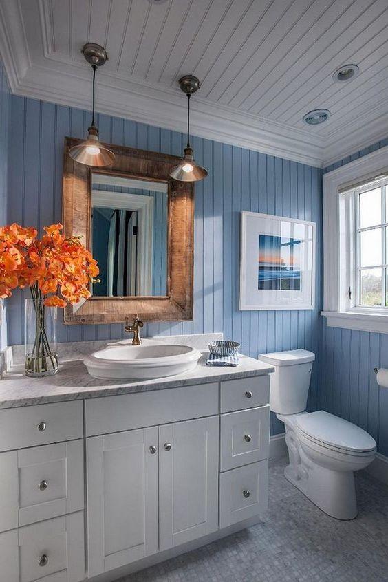 un moderno bagno ispirato al mare con un lavabo bianco, uno specchio con cornice in legno, lampade a sospensione e un'opera d'arte