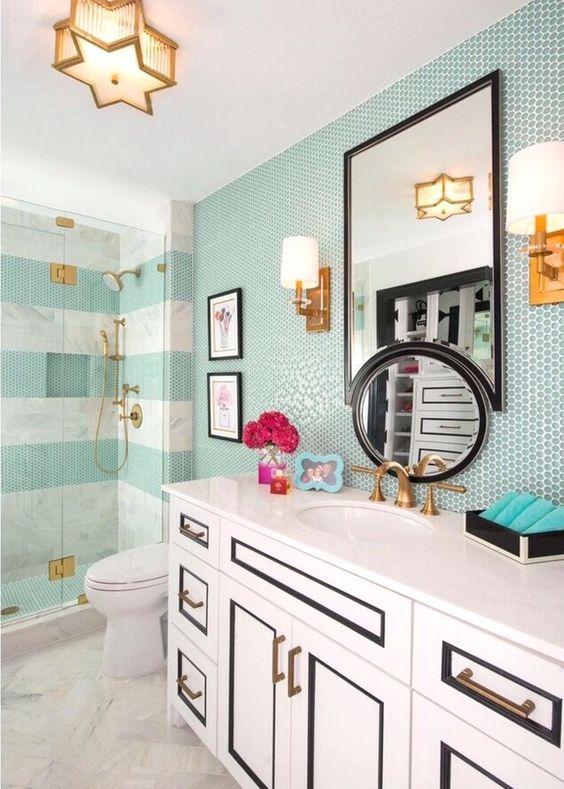 un bagno ispirato al mare con piastrelle aqua, un accattivante lavabo in bianco e nero e finiture dorate