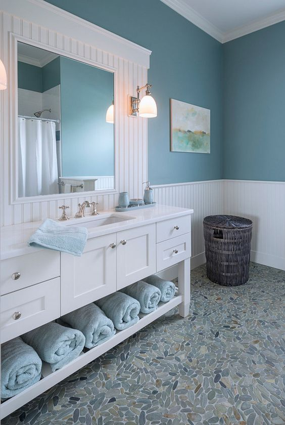 un bagno da fattoria sul mare con una grande vanità bianca e uno specchio, pareti blu e asciugamani e tocchi azzurri