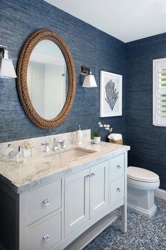 un bagno nautico con carta da parati in tessuto blu scuro, uno specchio ricoperto di corda e una vanità bianca più opere d'arte