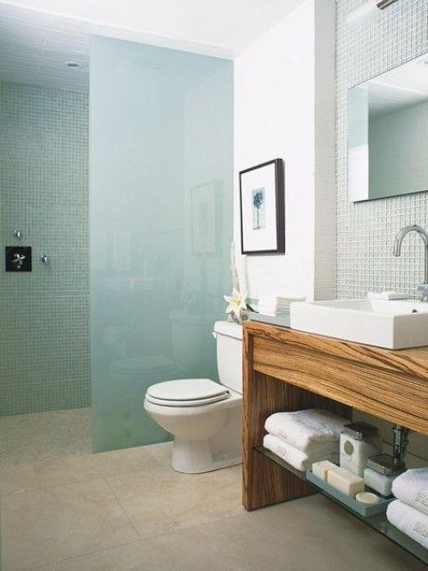 un bagno minimalista sulla spiaggia con piastrelle aqua sotto la doccia, un divisorio in vetro smerigliato e piastrelle verde chiaro sopra la vanità