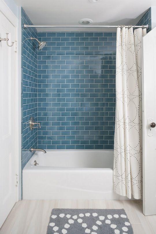 un bagno moderno e confortevole con piastrelle blu della metropolitana, una vasca bianca e tutti i neutri intorno