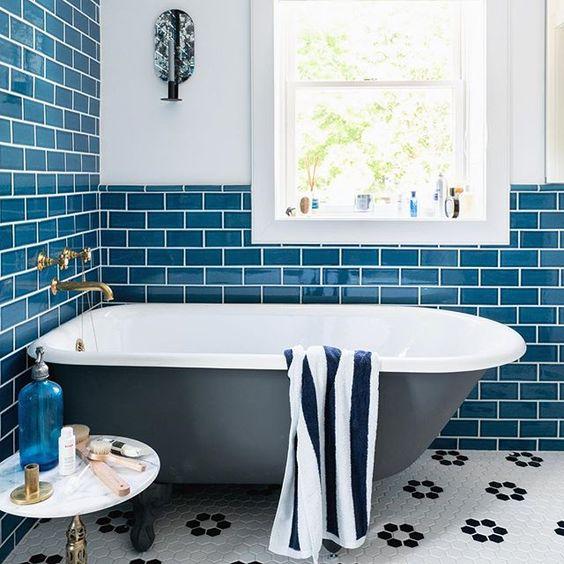 un bagno ispirato alla costa con piastrelle della metropolitana blu scuro, una vasca da bagno nera e alcuni accessori carini