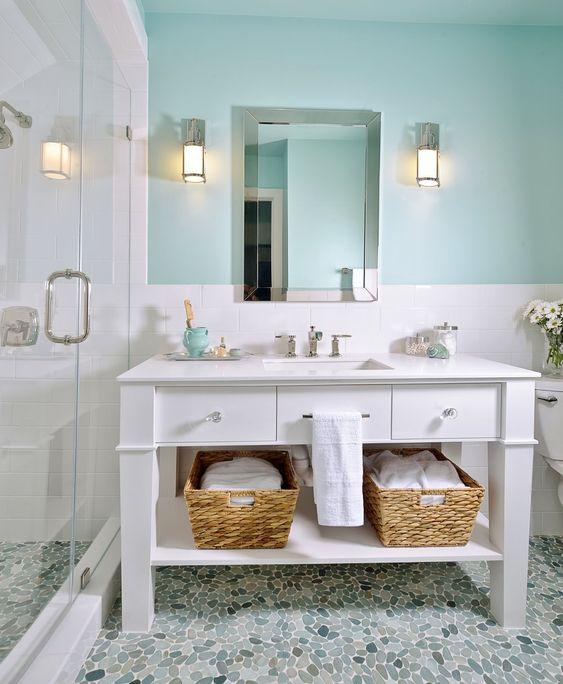 un bagno sulla spiaggia con una parete turchese, un lavabo bianco, cestini per riporre uno spazio accogliente