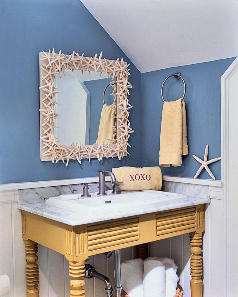 uno spazio lavandino divertente e stravagante con una vanità in legno vintage, uno specchio rivestito di stelle marine e semplici asciugamani (Marcus Gleysteen Architects)