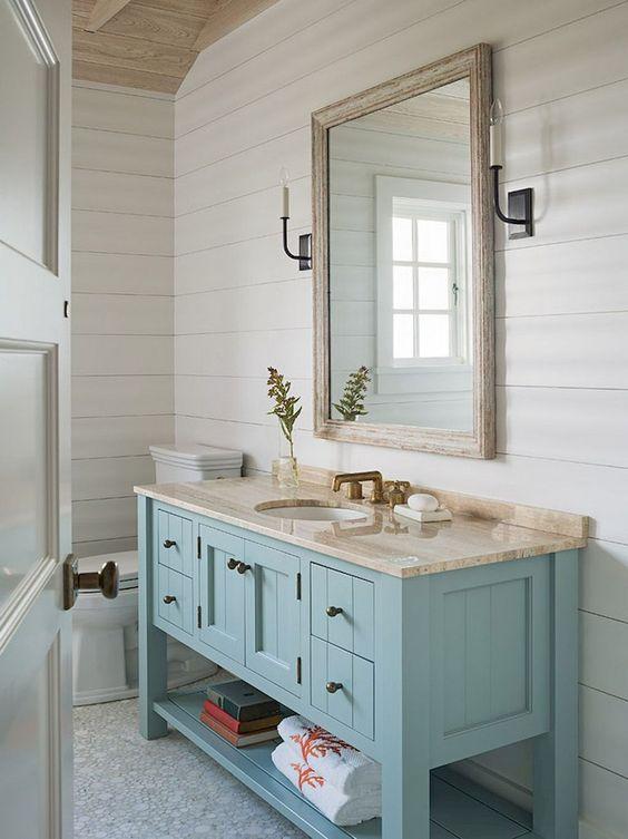 un bagno di ispirazione costiera con una vanità azzurra, uno specchio incorniciato e un fresco pavimento piastrellato