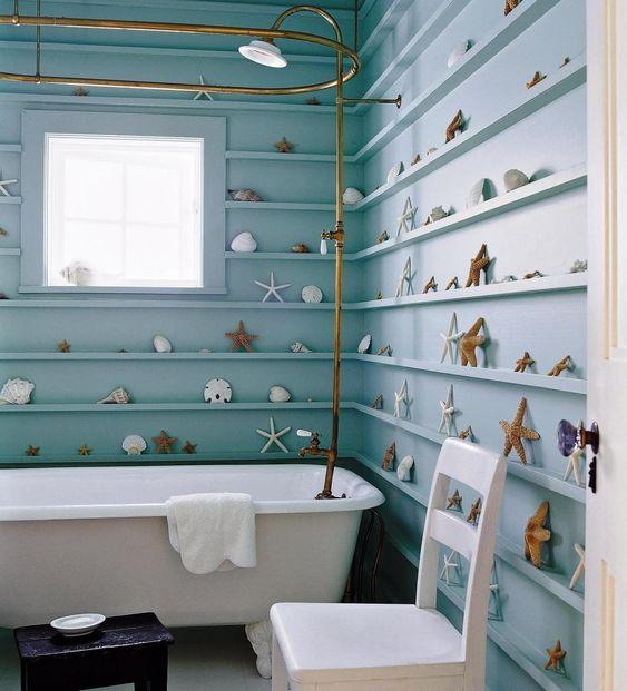 un bagno ispirato alla spiaggia con sporgenze per la visualizzazione di stelle marine, conchiglie e altri oggetti che creano un look chic