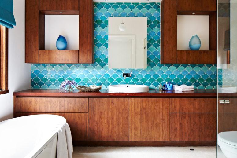 un bellissimo bagno ispirato al mare con mobili in legno dalle tinte ricche, piastrelle a squame di pesce turchese e blu e una vasca ovale (Camilla Molders Design)