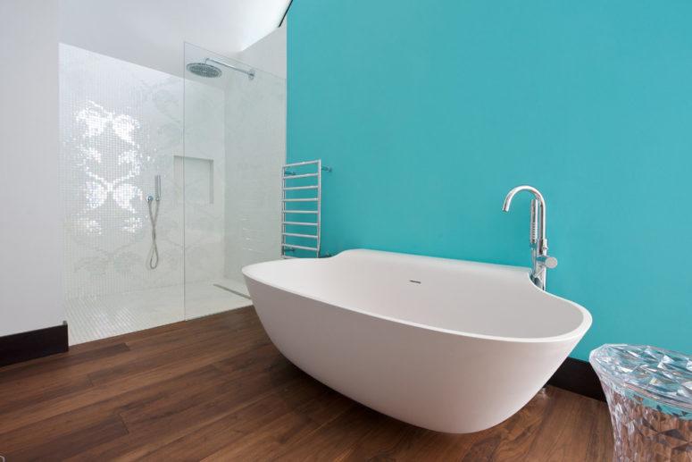 un bagno minimalista ispirato all'oceano con un muro turchese, una vasca dalla forma accattivante e piastrelle a mosaico nella doccia (Yorkshire Design Associates)