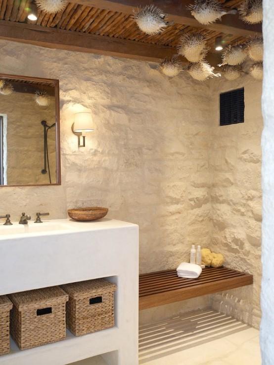 un bagno in spiaggia con rivestimento in pietra, un mobile lavabo bianco con cesti per riporre e pesci finti sospesi al soffitto