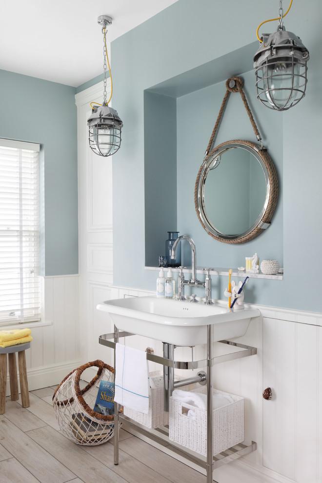 un bagno nautico con una mezza parete blu ardesia, un lavandino vintage, lampade a sospensione vintage e un pavimento in legno (Oliver Burns)