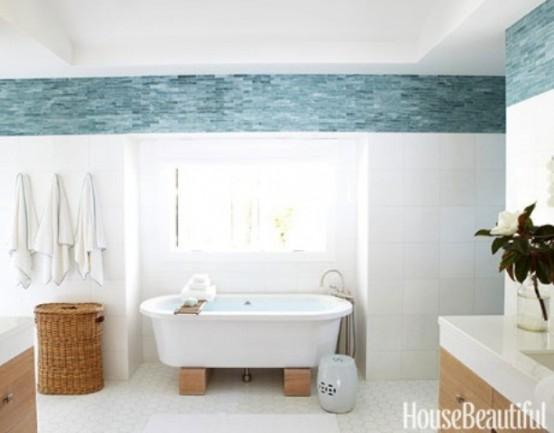 un bagno da spiaggia con decorazioni blu e bianche, mobili in legno e cesti per riporre gli oggetti