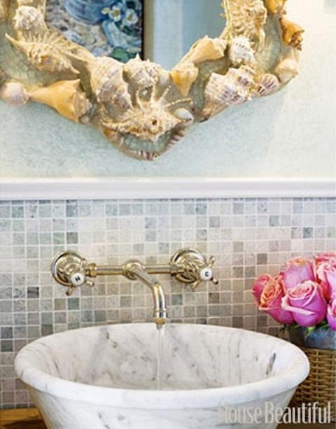 un lavabo in marmo e uno specchio rivestito di conchiglie e stelle marine per un bagno ispirato al mare